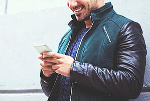 A man in a leather jacket looking at his mobile phone
