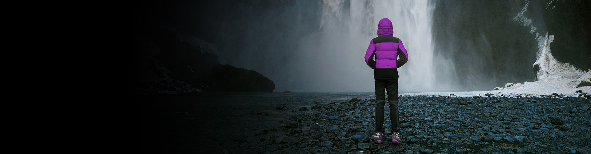 A young person in a padded jacket looking at a phenomenal waterfall