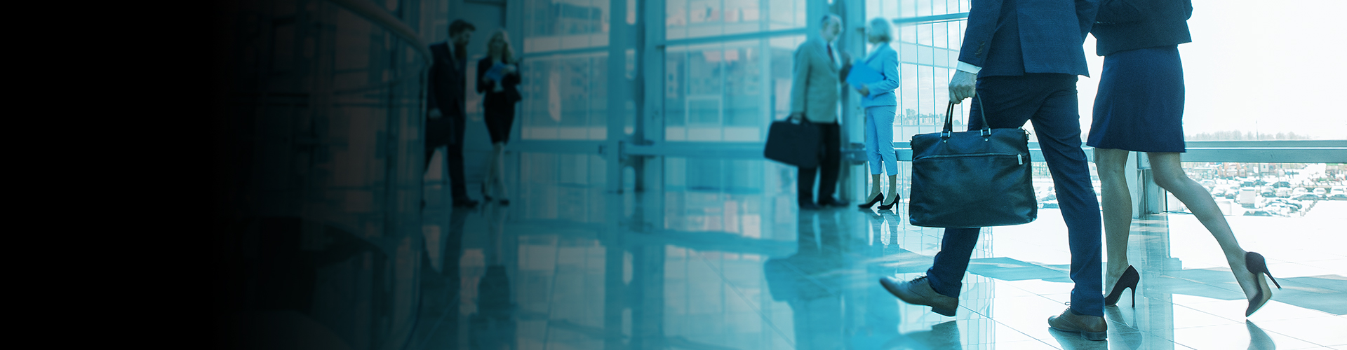 A man with a bag and a woman walking in an office building